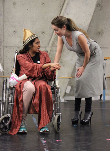 photo of woman in wheelchair wearing a party hat, speaking with a standing woman in high heels