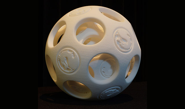 3D printed spherical puzzle with designs carved on both the inner and outer surfaces.