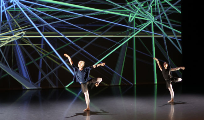 two ballet dancers on a stage with a backdrop of coloured geometric lines reflecting their poses