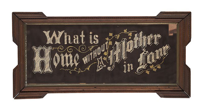 """Sampler with """"What is Home without a Mother in Law"""" stitched into the brown fabric with cream-coloured thread,, with a decorative wooden frame"""