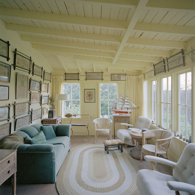 photo showing a sunroom with couch, chairs, and yellow walls hung with many framed needlework pieces