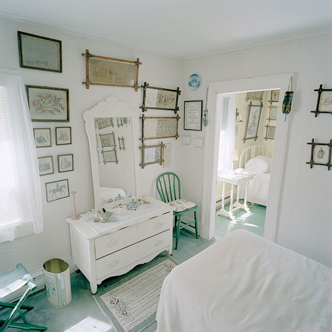photo of a bedroom with white furnituire and white walls, hung with many framed embroidered works