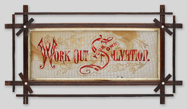 """The words """"Work Out Your Own Salvation"""" are stitched in red on a discoloured cream fabric, framed by a decorative wooden frame."""
