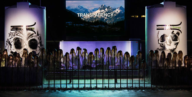 Night-time scene of projected images of a mountain with the word transparency over-written, flanked by scenes of human skulls, with viewers silhouetted in front of the images.