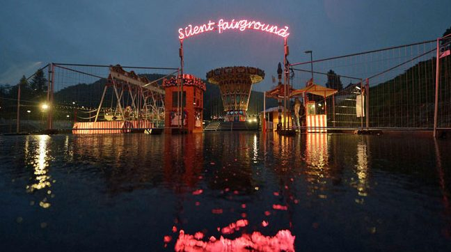 Night image showing a lit carousel and fairground attraction reflected in a body of water.