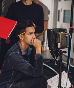 Alexander Desouza stares into video monitor on set of The Bump