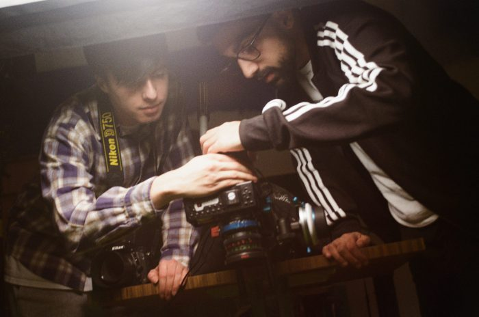 two filmmakers huddle over the camera