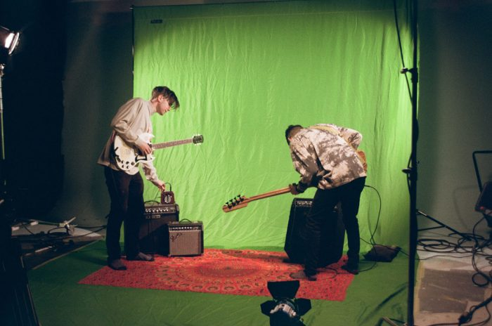 Still of two men playing electric guitar in front of a green screen