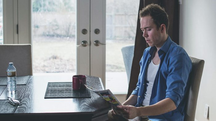 Man sits at kitchen table and stares concerned at a newspaper