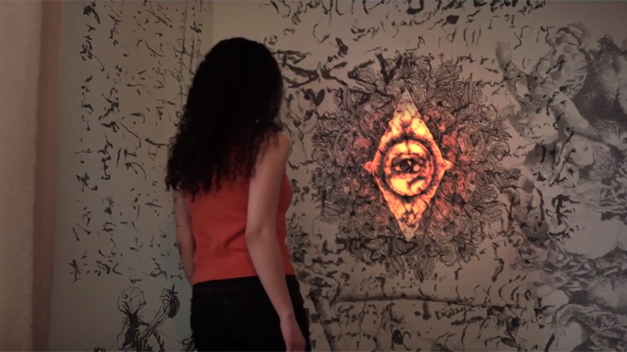 Woman dressed in red shirt and black pants, with back faceing the camera. She is staring at an orange glowing diamond shape covered in a design, appearing on the wall.