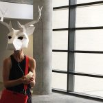 A woman in a hallway wearing a geometric white deer head mask