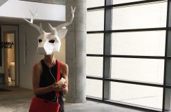 A woman in a hallway wearing a geometric white deer head mask