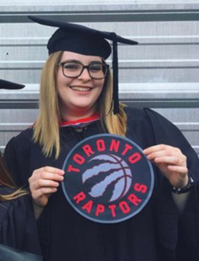 Dani de Angelis at Convocation holding a raptors sign