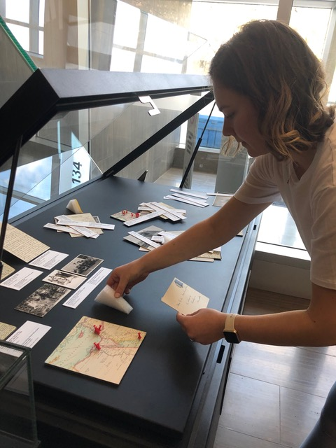 Christina installing the McLaughlin Family Mediterranean Cruise exhibit for the Archives of Ontario