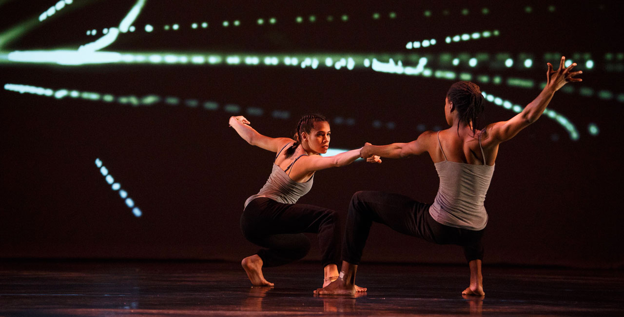 two dancers holding hands on darkened stage