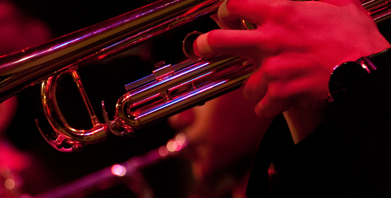 close up of 2 hands playing jazz trumpet