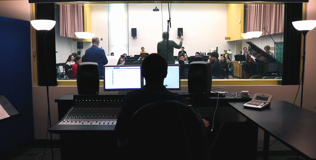 Student sits at audio controll board