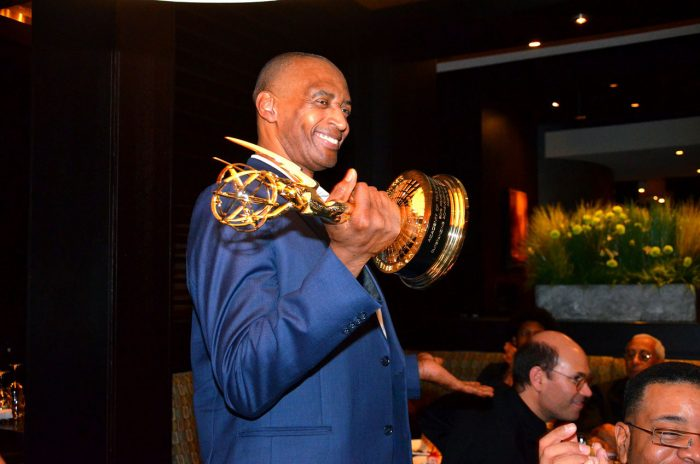 Ray Williams holds out his Emmy award and smiles.