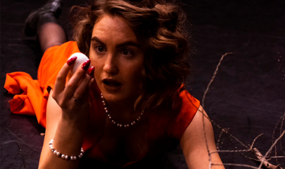 Photo of a woman in a red dress looking curiously at an egg in her left.
