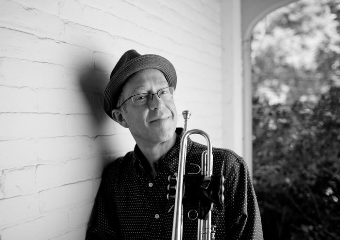 Dave Douglas smiles with his instrument in a greyscale photo