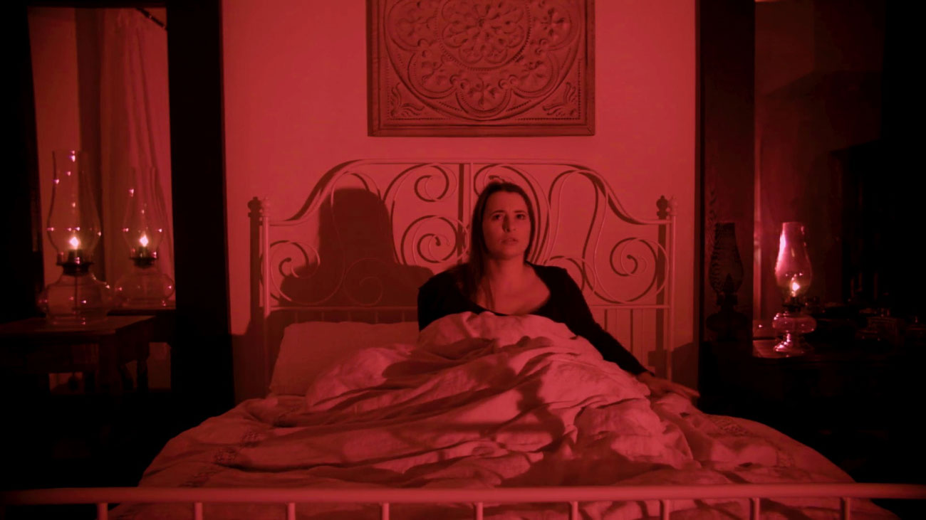 Woman in bed in a red room