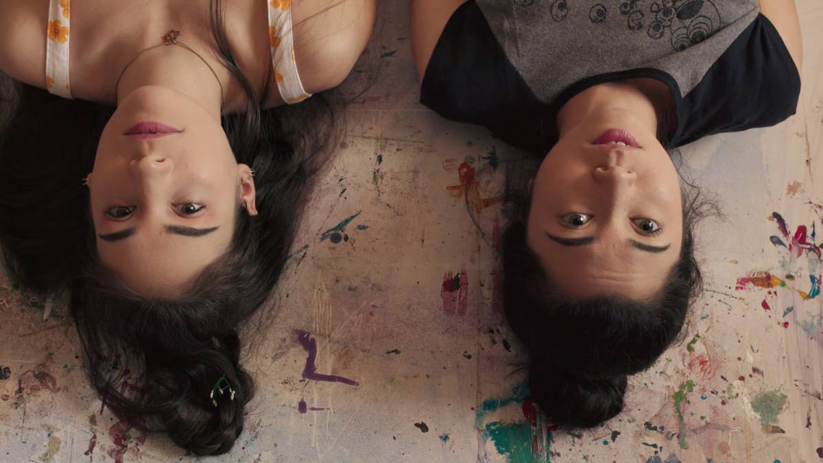 Two students lying side by side on the floor