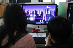 Two students play a video game on a desktop computer