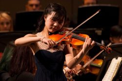 Violinist performs onstage with orchestra