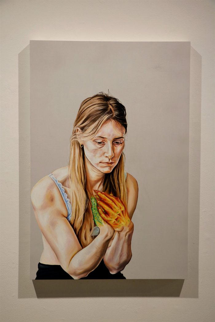 """All Good Things Must..."" by Serena Kobayashi-LeBel. Oil painting of blonde woman looking pensive clutching hands near her chest. Her hands and the veins within them resemble changing leaves."