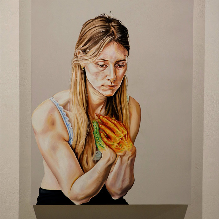 Painting by Serena Kobayashi-Lebel. A portrait of a young woman staring downwards, pensive, her hands have the coulour and veins of leaves.