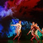 4 dancers wear clear plastic outfits as they dance in front of a galaxy projection in IM•MORTAL