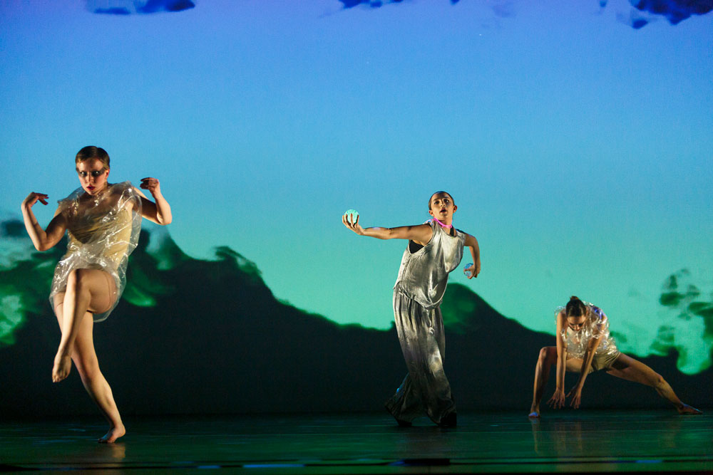 ancers wear clear plastic outfits as they dance in front of mountain projections in IM•MORTAL