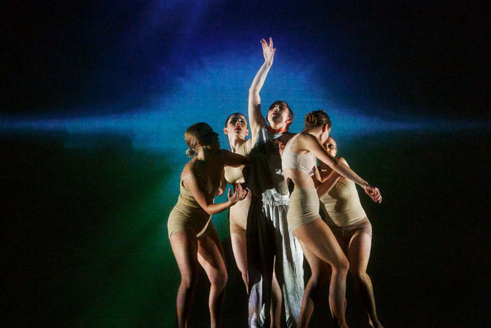 5 dancers pose in front of a burst projection in IM•MORTAL