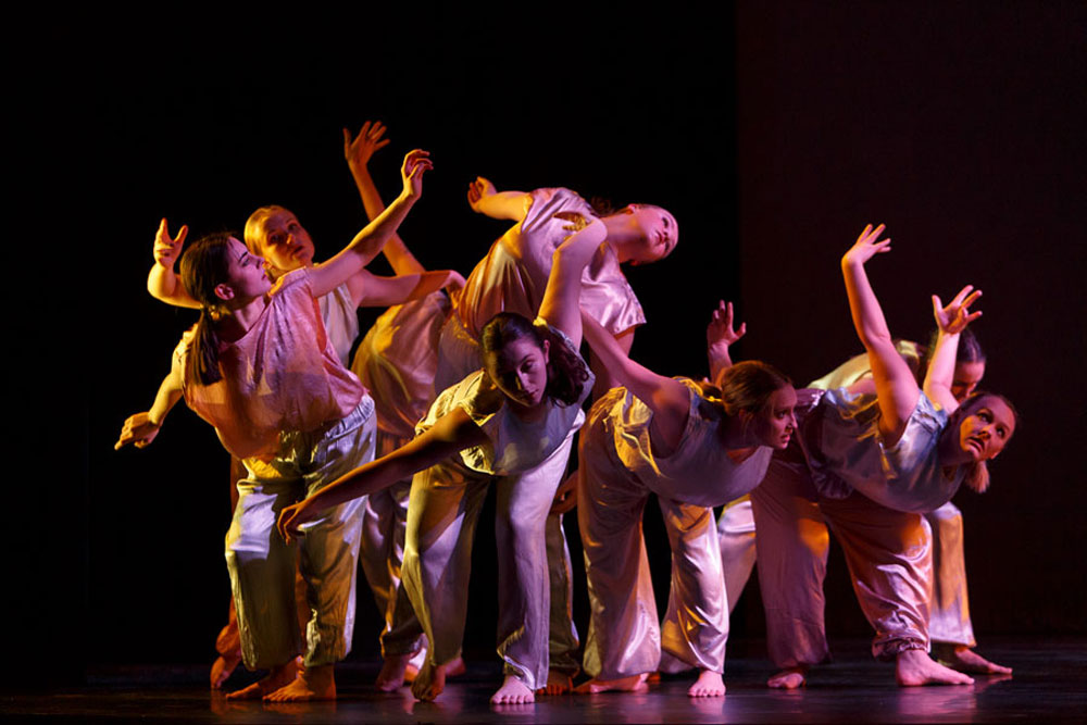 A group of dancers perform Jewels in the Sky under pink and yellow lights
