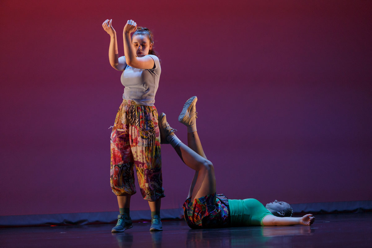 One dancer lies down with their feet on another dancer who is standing appear on stage in Pina Pt. 2