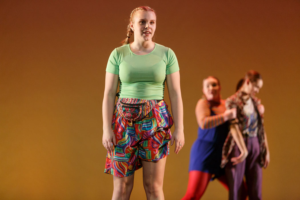 A dancer in green with two other dancers in the background appears on stage in Pina Pt. 2