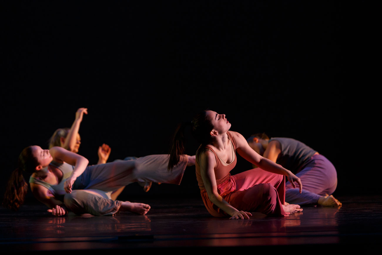 A group of dancers lie on stage in Theta Waves