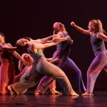 A group of dancers on stage in Theta Waves with pained faces