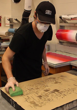 Student in a black shirt and baseball cap wears PPE in Visual Arts studio
