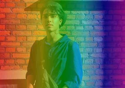 York Design student Jai Bhatia stands in front of a brick wall with a rainbow overlay.