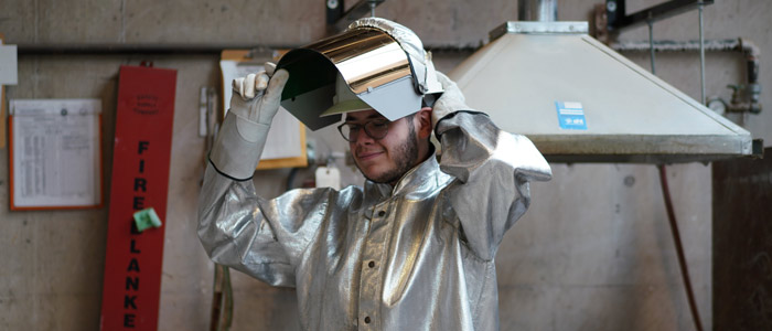 Moses Viveiros puts on protective gear in the sculpture studio