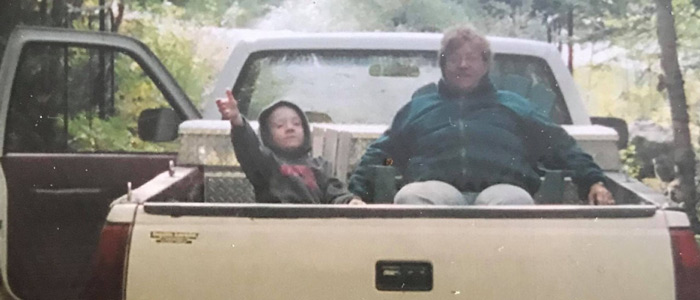 Garrett Ryan sits in the back of a yellow truck as a child in Northern Ontario with an adult