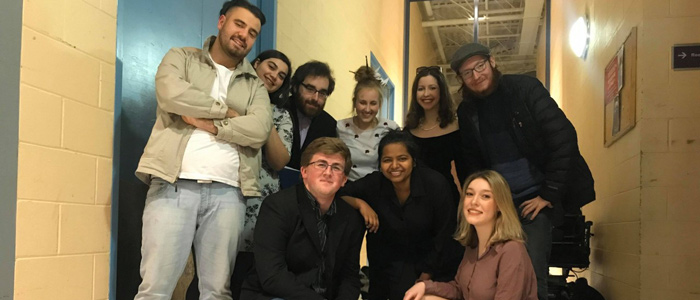 """Garrett Ryan (top right) with cast and crew for """"Off the Ground"""" in a York University hallway"""