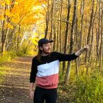 Garrett Ryan stands in a forest with yellow leaves in Northern Ontario