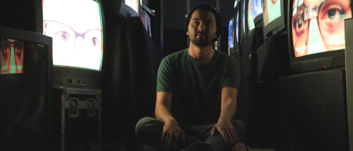 Amir Bahador Rostami sits between video screens