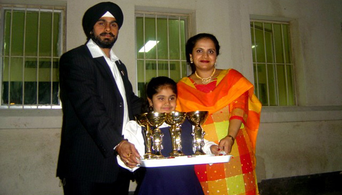 Gurharan Kaur as a child holding trophies with her mother and father