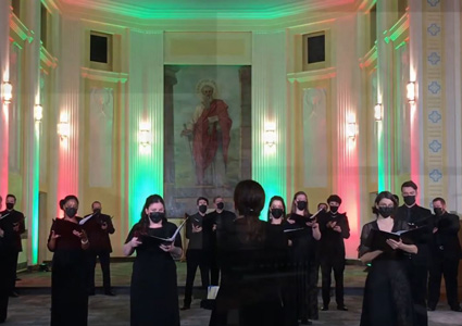 Lisette Canton leads a choir of masked singers in a large empty church.