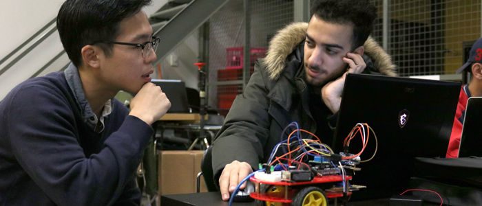 Two students converse by their laptop with a three-wheeled robot between them on the desk