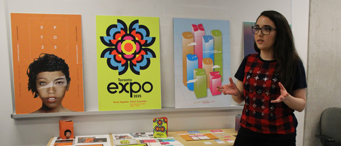 Young woman presents in front of posters she designed in class