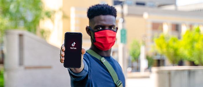 Student holds out cell phone with TikTok logo on the screen